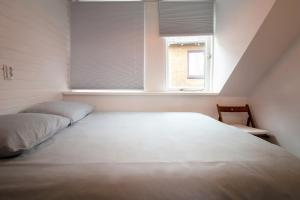 A bed or beds in a room at Carpe Diem Egmond aan Zee