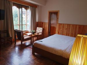 A bed or beds in a room at Khamsum Inn