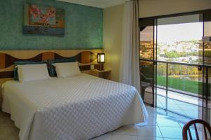 A bed or beds in a room at Hotel Lago Dourado