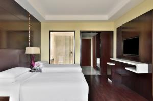 A bed or beds in a room at Jaipur Marriott Hotel