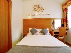 A bed or beds in a room at OYO Flagship Winford Manor