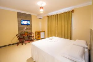 A bed or beds in a room at Vila Miola Hotel