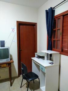 A television and/or entertainment center at Quarto Econômico com Banheiro sem café - Barão Geraldo - Prox UNICAMP