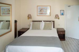 A bed or beds in a room at The Hannafore Point Hotel