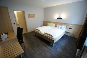 A bed or beds in a room at Hotel Restaurant Tychon AG