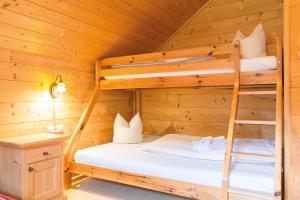 מיטה או מיטות קומותיים בחדר ב-Almdorf Reiteralm