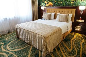سرير أو أسرّة في غرفة في فندق كازهول ألماتي