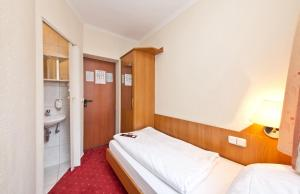 A bed or beds in a room at Hotel Primus Frankfurt Sachsenhausen