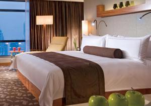 سرير أو أسرّة في غرفة في سويسأوتيل غراند شنغهاي