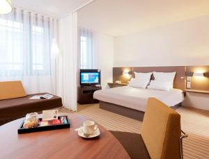 A bed or beds in a room at Novotel Suites Paris Velizy