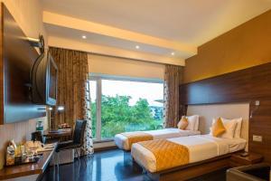 سرير أو أسرّة في غرفة في Flora Airport Hotel and Convention Centre Kochi