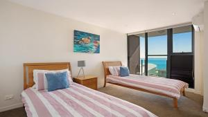 A bed or beds in a room at Strand Beachside 603