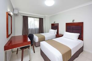 A bed or beds in a room at Best Western Casula Motor Inn