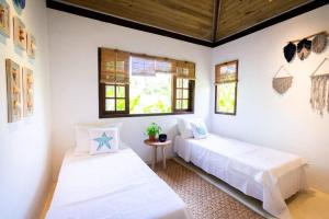 A bed or beds in a room at Casa Mariane Trancoso