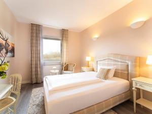Ein Bett oder Betten in einem Zimmer der Unterkunft Victor's Seehotel Weingärtner Bostalsee