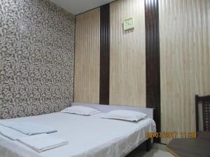 A bed or beds in a room at Hotel Vrindavan