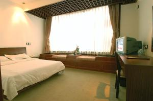 A bed or beds in a room at Shangfu Jiari Hotel Nanjing Pedestrian Street
