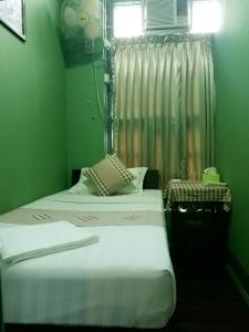 A bed or beds in a room at The SAT Yangon