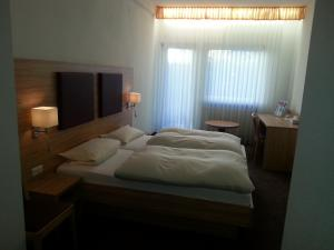 A bed or beds in a room at Hotel Rückert