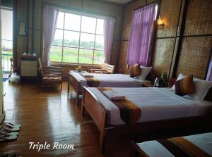 A bed or beds in a room at Moe Yun Gyi Resort