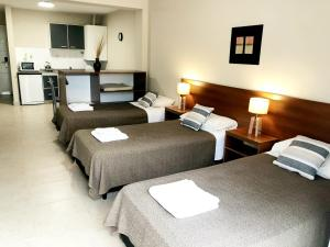 A bed or beds in a room at Soltigua Apart Hotel Mendoza