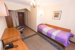 A bed or beds in a room at Pallada Hotel