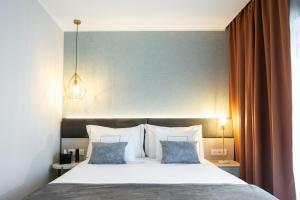 A bed or beds in a room at Duplo Charme Boutique Hotel