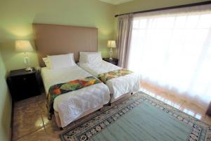 A bed or beds in a room at Emzini Apartments
