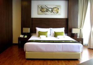 A bed or beds in a room at Samsuria Beach Resort & Residence