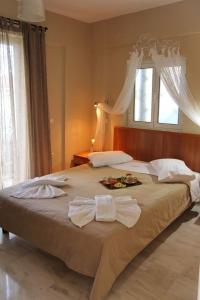 A bed or beds in a room at Ionian Riviera Hotel