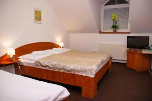 A bed or beds in a room at Penzion Axa