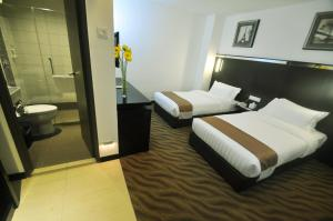A bed or beds in a room at Dreamtel Kota Kinabalu