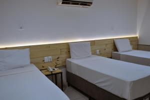 A bed or beds in a room at Aquamar Praia Hotel