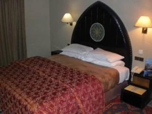 A bed or beds in a room at Le Tichka Ouarzazate