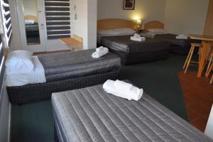 A bed or beds in a room at Warwick Vines Motel
