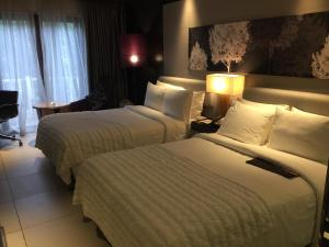 A bed or beds in a room at Le Meridien Mahabaleshwar Resort & Spa