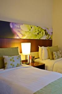 A bed or beds in a room at Somerset Kuala Lumpur