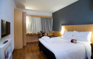 A bed or beds in a room at Ibis Vitoria Praia do Canto