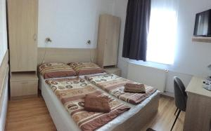 A bed or beds in a room at Gerendas Panzió