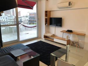 A television and/or entertainment center at Apart- Departamento totalmente equipado con terraza y parrilla privada