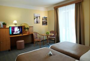 A bed or beds in a room at Act-ION Hotel Neptun – Terme & Wellness LifeClass