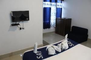 A television and/or entertainment centre at Say Rooms Hotel Riddhi Siddhi
