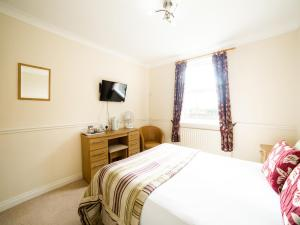 A bed or beds in a room at OYO White Horse Lodge Hotel