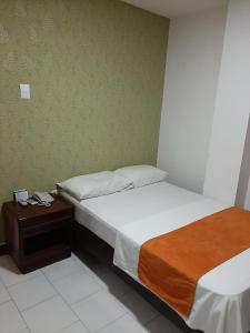 A bed or beds in a room at Hotel Exito Barranquilla