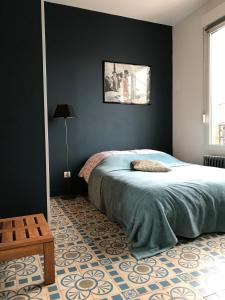 A bed or beds in a room at Aux Portes de Paris