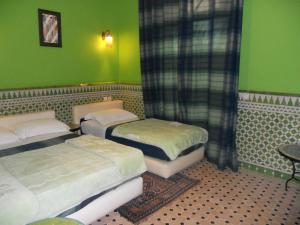 A bed or beds in a room at Riad Passiflora