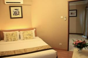 A bed or beds in a room at Grand Setiabudi Hotel