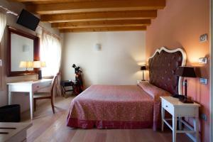 A bed or beds in a room at Hotel Asolo