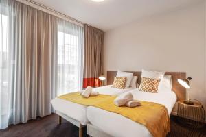 Un ou plusieurs lits dans un hébergement de l'établissement Appart'City Confort Lille Grand Palais