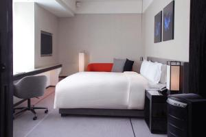 A bed or beds in a room at Humble House Taipei